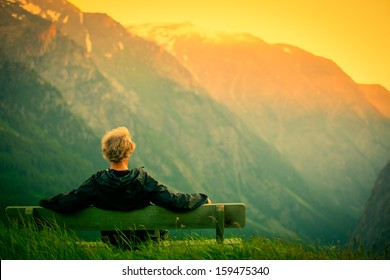 man sitting on bench in mountains