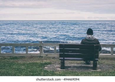 Man sitting on bench overlooking sea