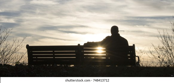 Man sitting on a bench in a park during sunrise.