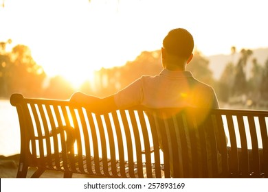 A man is sitting on a bench pondering life during a dramatic, warm sunset.