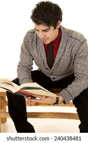 A man sitting on a bench studying a book