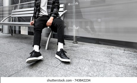man is sitting on a bench. Urban photo. Look book. Hype sneakers background. Best