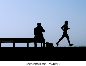Man sitting on bench watches jogger in dusk silhouette