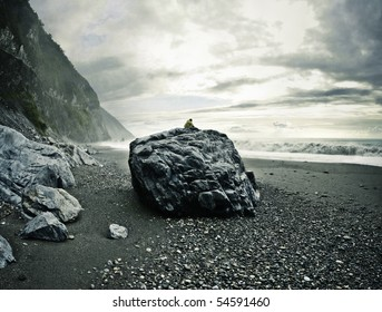 Man sitting on a big rock on a rocky beach watching the ocean. Location: Hualien County, Taiwan