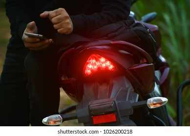 Man sitting on a bike & using mobile phone isolated stock photograph