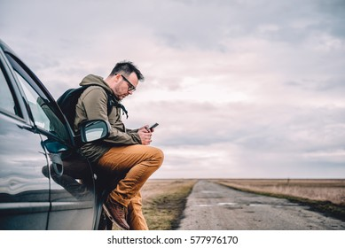 Man sitting on the car and using smart phone