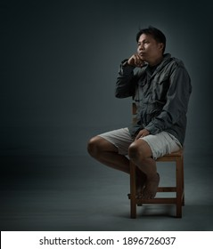 A man sitting on a chair in a dark room expressing emotions with loneliness