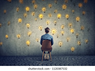 Man sitting on a chair has many bright ideas looking at wall making decisions