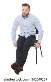 man sitting on chair. Isolated white background. legs crossed, holding to the seat