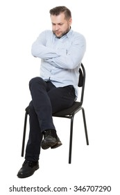 man sitting on chair. Isolated white background. Body language. gesture. Training managers. sales agents.  fully closed position. lowered eyes, drawn-neck, arms and legs crossed