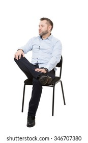 man sitting on chair. Isolated white background. Body language. gesture. Training managers. sales agents.  legs crossed, fixed arm. misses. dominant position.
