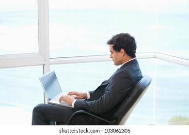 Man sitting on a chair while typing on a computer