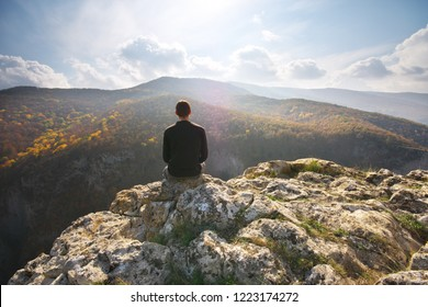 Man sitting on the cliff. Conceptual scene. Mountain nature edge composition.