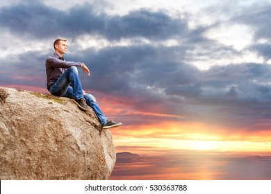 Man Sitting on a Cliff, Enjoying View of a Setting Sun over Firth of Clyde, Scotland
