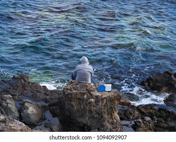 A man is sitting on a cliff for fishing.He has on a blue-gray hooded jacket, under him the moving Atlantic. An image that radiates calm in the colors blue.