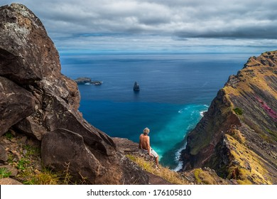 Man sitting on a cliff looking out over the sea at the rim of the crater of Rano Kao, Easter Island, Chile