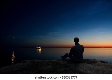 Man Sitting on a Cliff Watching Sea, Ship and Setting Moon