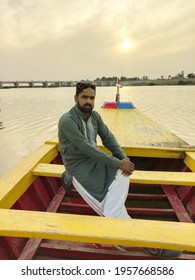 man sitting on colorful wooden boat,evening view at head Saifan melsi Pakistan,tourism and picnic point