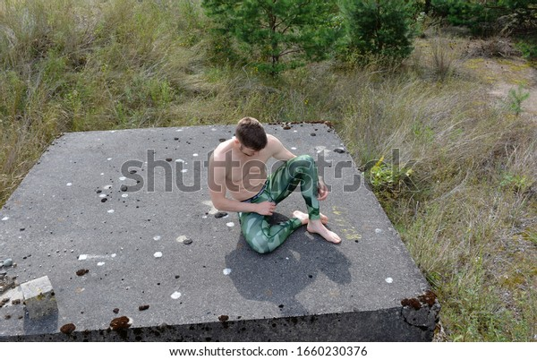Man Sitting On Concrete Cube Among  Grass