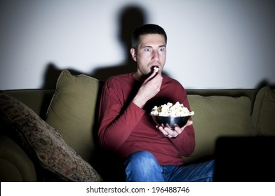 A man sitting on a couch eating popcorn.