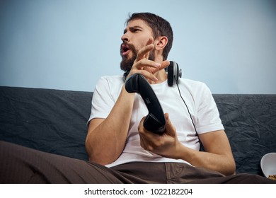 man is sitting on the couch with headphones, joystick on a blue background
