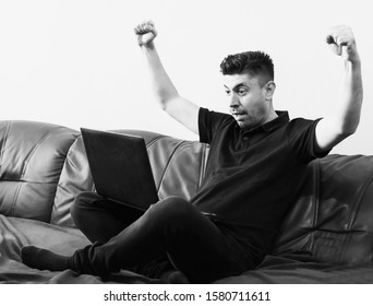 The man is sitting on the couch with his laptop in front.Happy excited caucazian man holding laptop and raising his arms up to celebrate success. He won