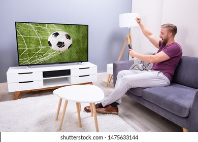 Man Sitting On Couch Watching Soccer Game On Television At Home