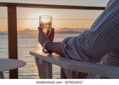 Man sitting on deck chair at sunset holding a alcoholic drink with ice in hand while gazing at sea wearing wristwatch