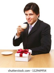 Man sitting on the desk with cup of coffee, gift on the desk