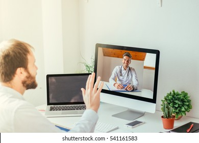Man sitting on desk videoconferencing with doctor on computer at home.
