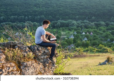 a man sitting on the edge of a cliff and reading a book