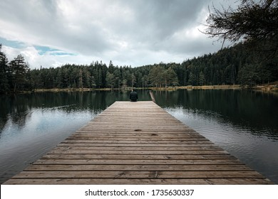 man sitting on the end of a pier jetty looking out to the water in a lake in a forest on a gloomy cloudy day