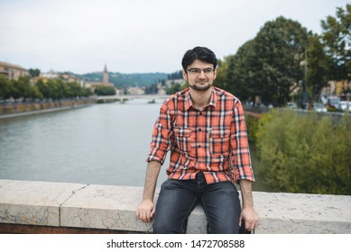 man sitting on fence of bridge over river in Italy