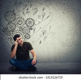 Man sitting on the floor hard thinking, find a solution to solve problem. Different imagination, alternative idea. Gear brain arrows and mess as thoughts. Concept for mental, psychological development