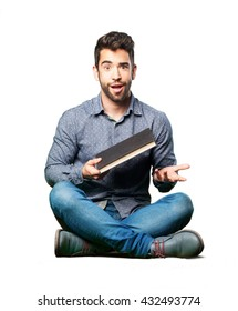 man sitting on the floor holding a book