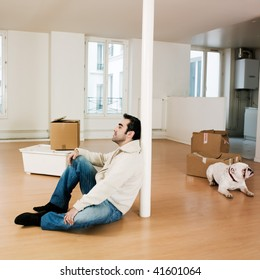 man sitting on the floor inside an empty loft apartment with tax forms and laptop computer