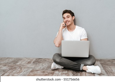 Man sitting on the floor with laptop and talking at phone. Isolated gray background