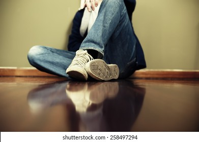 Man sitting on floor leaning on the wall. Very shallow depth of field, edited with vintage colors