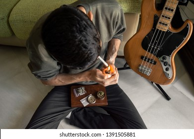 Man sitting on the floor smokes a marihuana joint at home after playing the bass. Rolling a joint. Grinder, paper and weed on a book.