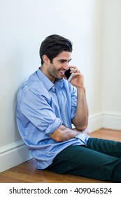 Man sitting on floor and talking on phone at home