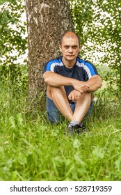 a man is sitting on the grass near a tree