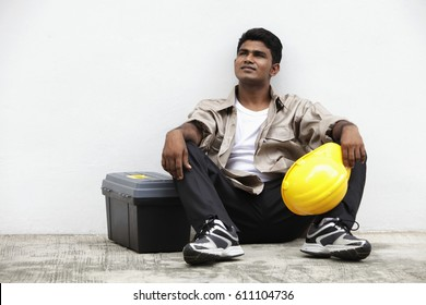 man sitting on ground holding construction hat