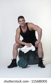 man sitting on a gym ball holding a towel after doing a work out