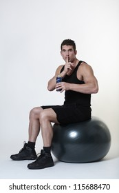 man sitting on a gym ball not sure if he should have a beer instead of finishing his workout
