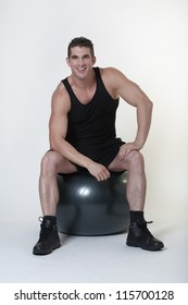 man sitting on a gym ball looking at camera with a big smile on his face