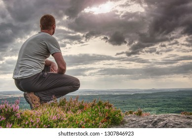 Man sitting on hill summit. Conceptual scene. He was wearing light outdoor clothes. He was looking forward with determination