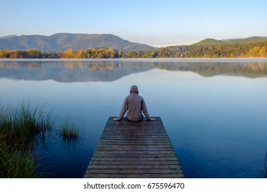 man sitting on his back on a pier at sunrise
