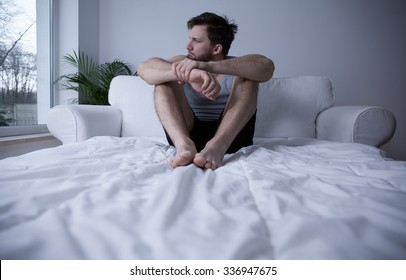 Man sitting on his bed in the morning