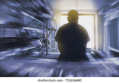 Man sitting on the hospital bed looking through the window, concept of dying patient.
