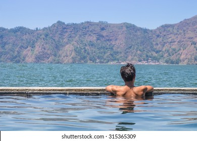 A man sitting on the hot spring pool where located beside the beautiful lake of Batur mountain, Bali, Indonesia